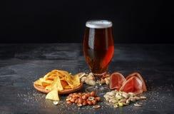 啤酒和咸快餐在一张黑桌上 与坚果和芯片的酒精饮料 庆祝概念查出的白色 传统快餐 库存照片