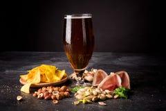 啤酒和咸快餐在黑背景 与坚果和芯片的酒精饮料 传统快餐 复制空间 免版税库存图片