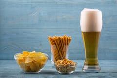 啤酒和快餐、芯片、面包条和花生 图库摄影