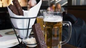 啤酒和快餐在木背景 免版税库存照片