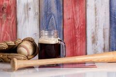 黑啤酒和棒球材料与被绘的退色的木板  库存照片