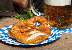 啤酒和椒盐脆饼在一个纸碟 免版税库存照片