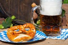 啤酒和椒盐脆饼在一个纸碟 图库摄影