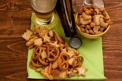啤酒和盐味的快餐在木背景 库存图片