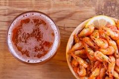啤酒和虾在碗在木背景 杯啤酒和大虾 侥幸 免版税库存图片