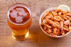 啤酒和虾在碗在木背景 杯啤酒和大虾 侥幸 免版税库存照片