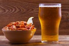 啤酒和虾在碗在木背景 杯啤酒和大虾 侥幸 图库摄影