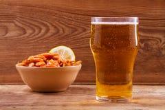 啤酒和虾在碗在木背景 杯啤酒和大虾 侥幸 免版税图库摄影
