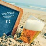 啤酒和黑板有文本的欢迎夏天,在沙子  免版税库存图片