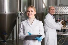 啤酒工厂的两名啤酒厂工作者 免版税库存图片