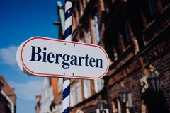 啤酒庭院标志 被打开的盾用德语biergarten一个晴朗的假日 老传统德国buildung在背景中 免版税库存图片