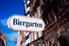 啤酒庭院标志 被打开的盾用德语biergarten一个晴朗的假日 老传统buildung和蓝天 库存照片