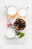 啤酒快餐集合 两个杯子比尔森啤酒、黑麦面包油煎方型小面包片、大蒜乳脂干酪调味汁和新鲜的草本在被绘的白色 免版税库存图片