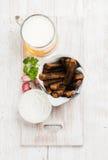 啤酒快餐集合 品脱在杯子和黑麦面包油煎方型小面包片的比尔森啤酒用大蒜乳脂干酪调味汁为新鲜的草本服务  库存图片