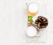 啤酒快餐集合 品脱在杯子的比尔森啤酒和黑麦面包油煎方型小面包片用大蒜乳脂干酪调味在老白色被绘 库存照片