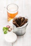 啤酒快餐集合 品脱在杯子的比尔森啤酒和黑麦面包油煎方型小面包片用大蒜乳脂干酪调味,在白色的新鲜的荷兰芹 免版税图库摄影