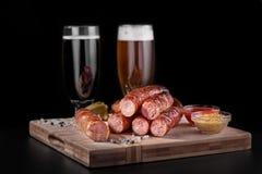 啤酒快餐,原始的香肠用与两杯的一个调味汁啤酒 图库摄影