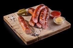 啤酒快餐,原始的香肠用调味汁 在一个木板上,在黑背景 库存照片