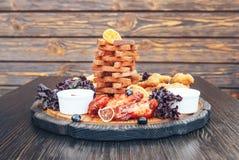 啤酒快餐 对啤酒薄脆饼干的快餐,乳酪黏附,鸡翼,油炸肉 库存图片