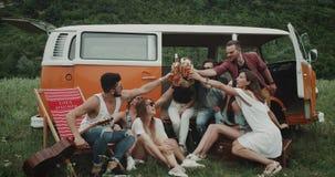 啤酒时间四一个大小组在自然中间的朋友,坐此外一辆减速火箭的橙色公共汽车,饮用的啤酒和 股票录像