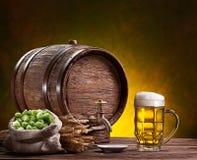 啤酒杯、老橡木桶、麦子耳朵和蛇麻草。 免版税库存照片