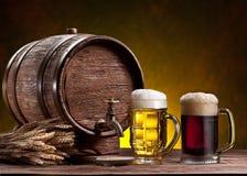 啤酒杯、老橡木桶和麦子耳朵。 图库摄影