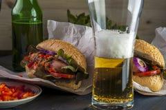 啤酒杯和两根热狗用烤香肠和菜 图库摄影