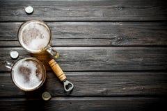 啤酒杯和开启者 库存图片