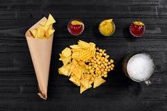 啤酒杯和快餐顶上的看法用调味汁在黑木桌上 免版税库存图片