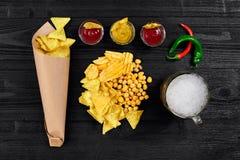 啤酒杯和快餐顶上的看法用调味汁在黑木桌上 图库摄影