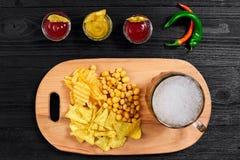 啤酒杯和快餐顶上的看法用调味汁在黑木桌上 免版税图库摄影