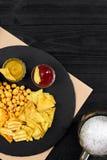 啤酒杯和快餐顶上的看法用调味汁在黑木桌上 库存图片