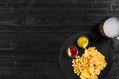 啤酒杯和快餐顶上的看法用调味汁在黑木桌上 免版税库存照片