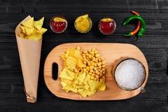 啤酒杯和快餐顶上的看法用调味汁在黑木桌上 库存照片