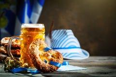 啤酒杯和椒盐脆饼在一张木桌上 Oktoberfest啤酒节日 库存照片