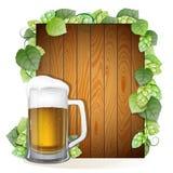 啤酒杯和蛇麻草在木背景分支 免版税库存照片