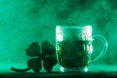 啤酒杯用绿色啤酒和三叶草在烟 图库摄影