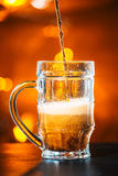 黑啤酒涌入一个玻璃杯子 库存图片