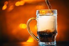 黑啤酒涌入一个玻璃杯子 免版税图库摄影