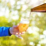 啤酒涌入了玻璃 免版税库存照片