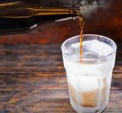 啤酒涌入从棕色瓶的一块冻玻璃在黑暗的wo 免版税库存照片