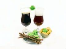 啤酒烈性黑啤酒和红色啤酒在玻璃与绿色三叶草与熟食店 免版税库存图片