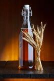 啤酒瓶仍然寿命与麦子束的 图库摄影