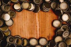 啤酒瓶加盖在木背景的框架 库存图片