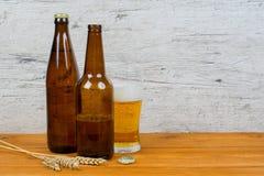 啤酒瓶和玻璃在客栈桌上 库存照片