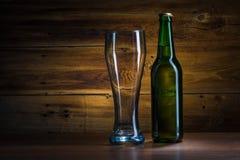 啤酒瓶和空的玻璃 免版税库存图片