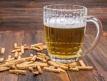 啤酒用在木背景的油煎方型小面包片 库存图片
