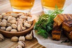 啤酒用开心果和油煎方型小面包片在一张木桌上 库存照片