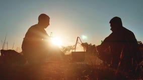啤酒由篝火坐生活方式的两个游人做在一个智能手机党的selfie在自然野营的剪影阳光下 股票视频