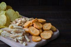 啤酒的快餐在桌上在客栈 花生,鱼,薄脆饼干,芯片 特写镜头 免版税库存照片
